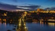 Prague, Czech Republic, zoom out time lapse view of Prague cityscape including historical landmarks Prague Castle and Charles Bridge over the Vltava River at sunset.