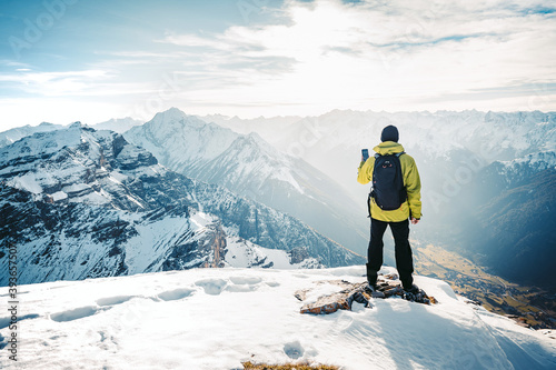 Obraz Climber take a mountain landscape photo on his smart phone. Hiker with backpack standing on top of a mountain and enjoying view. Tourist walk in the snow in the mountains during the winter holidays. - fototapety do salonu