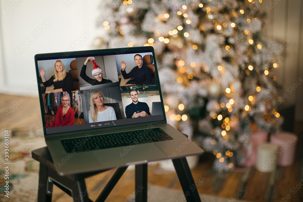 Fototapeta Virtual Christmas tree meeting team teleworking. Family video call remote conference. Laptop webcam screen view. Team meet working from their home offices. Happy hour party online woman team diversity