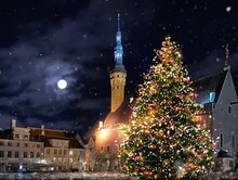 Christmas Tree Illuminated Decoration  On Hall Town Square In Winter  Tallinn Old Town Medieval City ,moon On Night Blue Sky Snow Fall ,holiday In Estonia