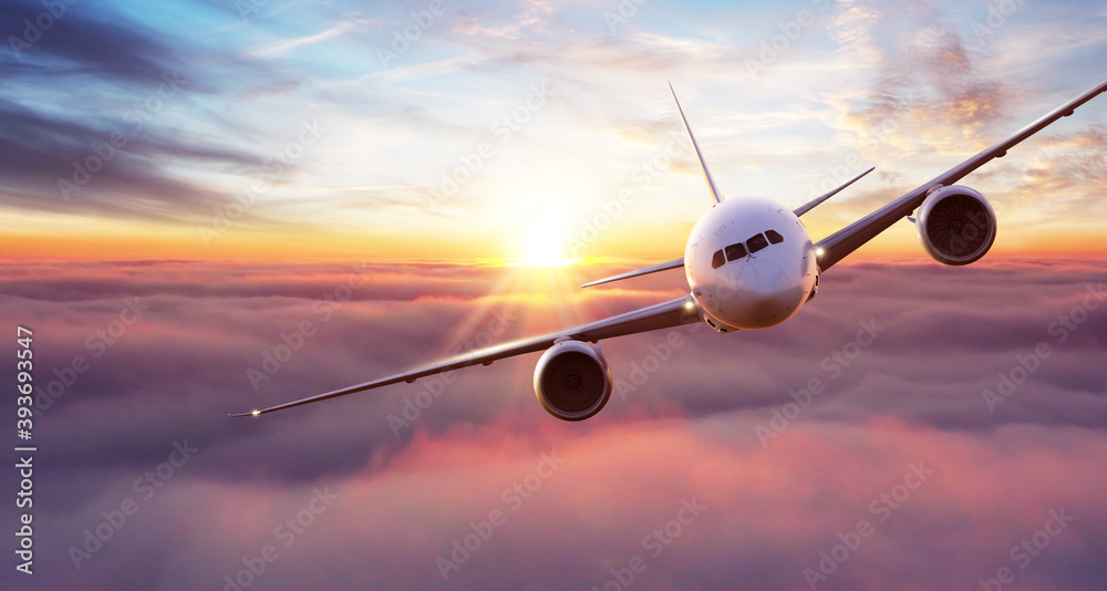 Fototapeta Commercial airplane flying above clouds in dramatic sunset light.