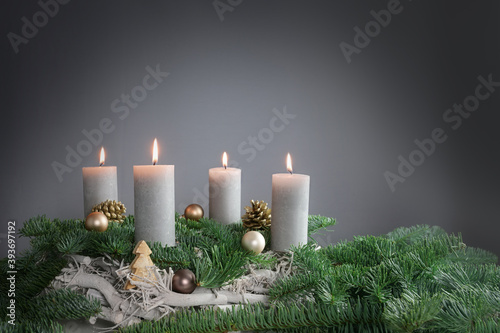 Four candles are burning for the fourth Advent on fir branches with Christmas decoration against a grey background, copy space