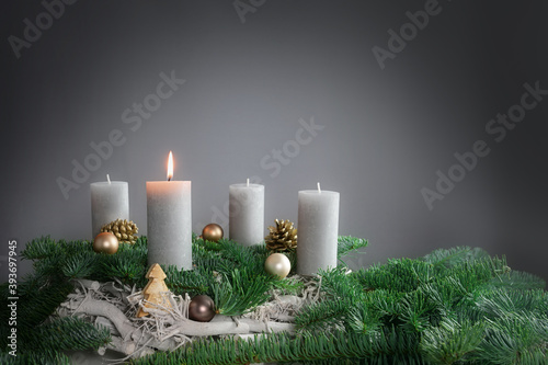 One of four candles is burning for the first Advent on fir branches with Christmas decoration against a grey background, copy space