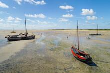 Flatbottom Sailing Ships Beached On The Noordsvaarder Nature Reserve On The Island Of West-Terschelling, Friesland, Netherlands