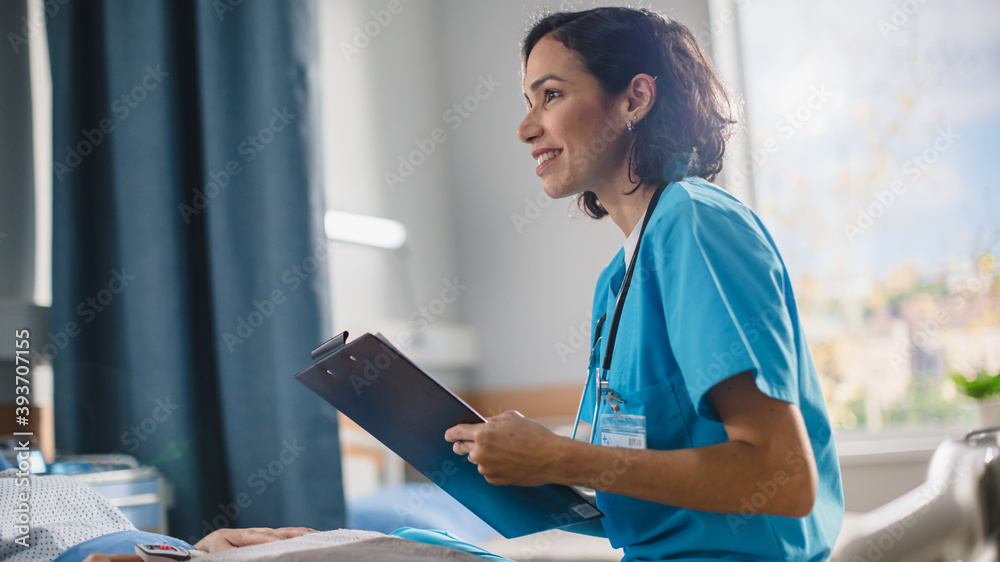 Fototapeta Hospital Ward: Portrait of Friendly Hispanic Head Nurse Fills Medical History Form, Talks to Anonymous Patient Recovering in Bed. Doctor Helps Person Get Better. Close-up Portrait Shot.