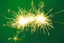 Bright Burning Sparklers On Green Background, Closeup