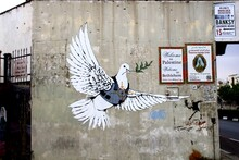 Bird Flying Against The Wall Made By Banksy In Bethlehem
