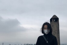 Portrait Of Young Woman Wearing Mask Standing Against Sky