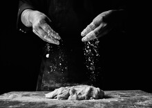 Midsection Of Chef Preparing Food Against Black Background
