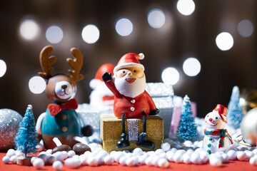 Santa Claus doll, pine tree, deer, snowman and gift box Christmas decoration on a bokeh light background with copy space