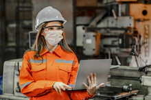 Portrait Of Engineer Wearing The Face Mask And Holding Laptop With Blurred Factory Machinery Background