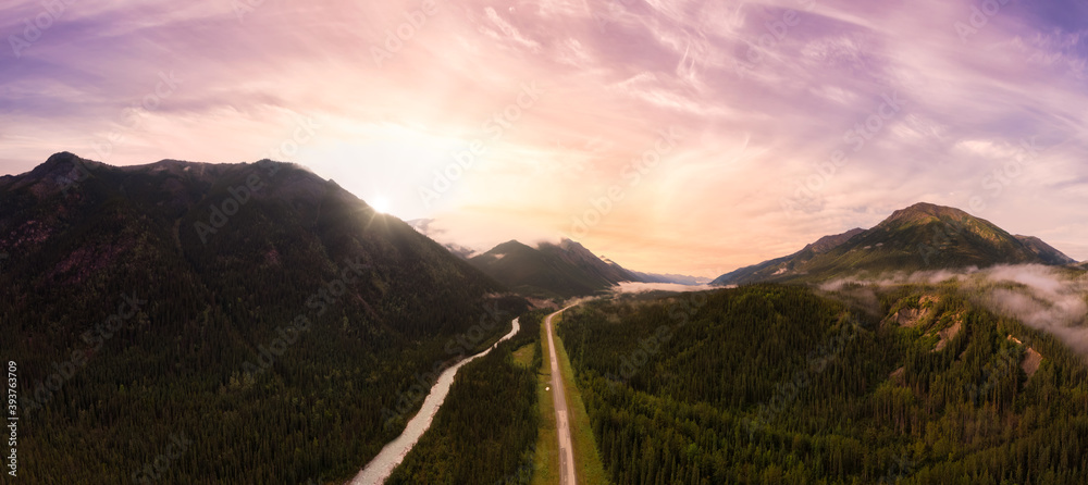 Fototapeta Picturesque Panoramic View of Scenic Road from Above alongside Winding Glacial River. Dramatic Sunrise Sky. Aerial Drone Shot. Alaska Highway in the Northern Rockies, British Columbia, Canada.