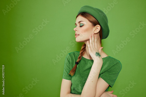 Photo Nice girl with a shamrock on her hand on a green background holidays St