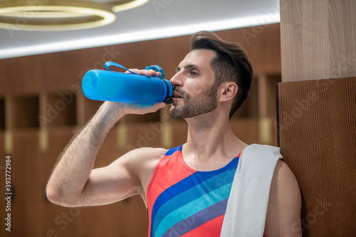 Obraz na plátně Young man in bright tshirt feeling thirsty after workout