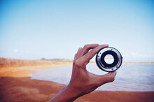 Cropped Hand Holding Camera Lens At Beach Against Sky