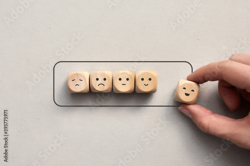 Fotografiet Wooden cubes with drawings of various emotions show the battery loading