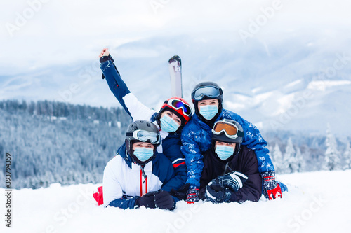 Fototapeta premium Group of happy friends having fun. Young people with face mask during COVID-19 coronavirus on a snowy mountain at a ski resort