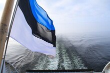 Close-up Of Flag Waving In Boat On Sea Against Sky