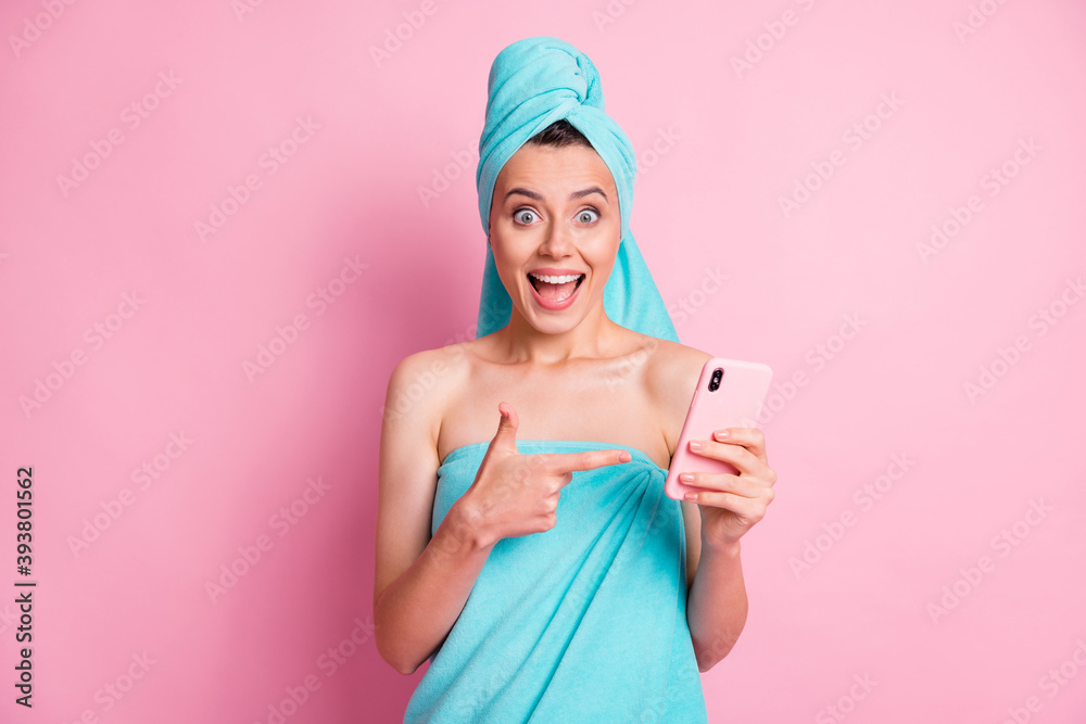 Fototapeta Portrait of hooray sweet young lady pointing telephone wear teal towels isolated on pastel pink color background