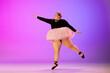 Leinwandbild Motiv Confidence. Beautiful caucasian plus size model practicing ballet dance on gradient purple-pink studio background in neon light. Concept of motivation, inclusion, dreams and achievements.