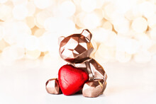 Gift Card With Chocolate Bear Holding Red Heart On Golden Background Of Christmas Lights Bokeh. Mockup For Decorative Design. Christmas And New Year Concept. Copy Space.