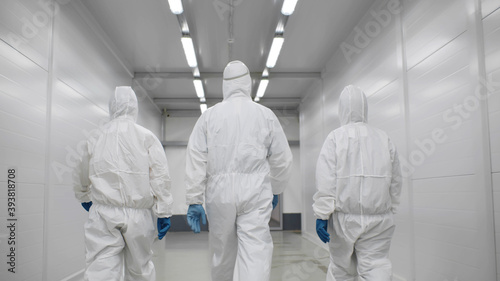 Stampa su Tela Back view of three disinfectors or doctors walk in protective uniform walking in
