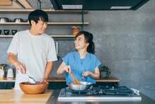 キッチンで料理する夫婦