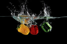 Close Up View Of Color Pepper Vegetable Falling Into Water Isolated On Black Background