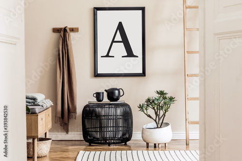 Japandi style living room with mock up poster frame, design wooden commode, unique furniture, decoration and elegant personal accessories. Neutral interior in scandinavian house. Cozy home decor.