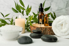 Beauty Treatment Items For Spa Procedures On White Wooden Table With Green Plant. Massage Stones, Essential Oils And Sea Salt With Burning Candle