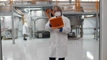 Mature Engineer Wearing Lab Coat And Using Tablet At Chemical Production Plant