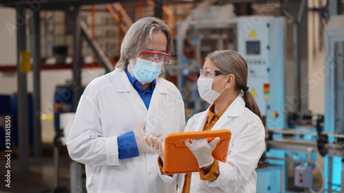 Man and woman in white robe and safety mask in production department of chemical Wallpaper Mural