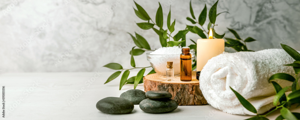 Fototapeta beauty treatment items for spa procedures on white wooden table. massage stones, essential oils and sea salt. copy space