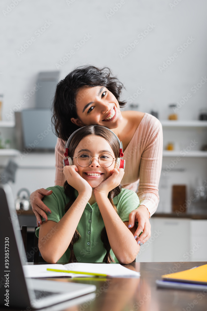Fototapeta Smiling hispanic woman hugging daughter sitting at table with laptop in kitchen on blurred foreground