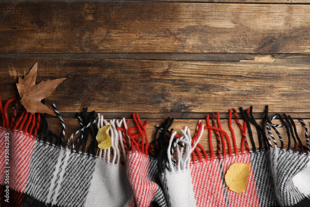 Fototapeta Checkered plaid and dry leaves on wooden table, flat lay. Space for text