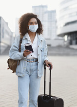 Young Woman Tourist Holding Passport And Ticket, Girl Wearing Protective Face Mask In A City, Business Travel During Pandemic, Corona Virus Protection, Healthy Lifestyle, People, Tourism Concept