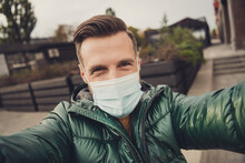 Photo Of Cute Good Mood Young Guy Dressed Green Coat Protection Mask Making Selfie Outdoors City Street