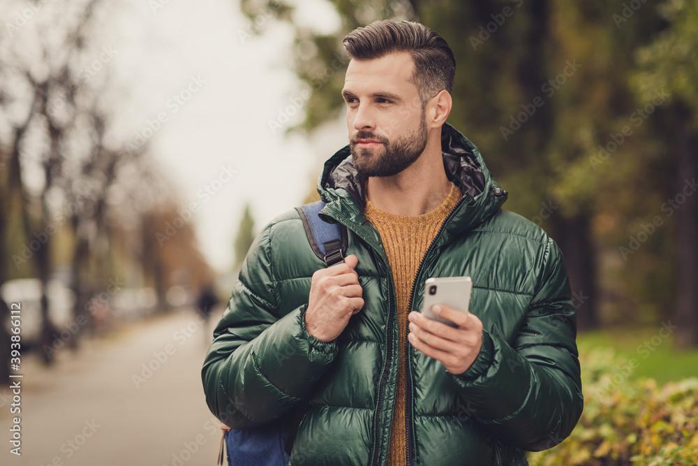 Fototapeta Portrait of good looking young guy hold rucksack look far away good mood autumn travel sightseeing outdoors