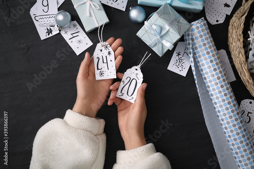 Woman making advent calendar at black table, top view