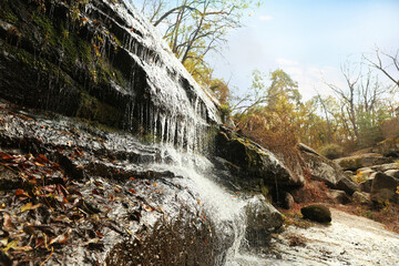 Picturesque view of beautiful waterfall in forest on autumn day