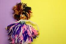A Loose Wool Doll Wearing Purp...