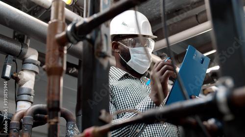 Obraz na plátně African mechanical supervisor in safety mask doing inspection on plant