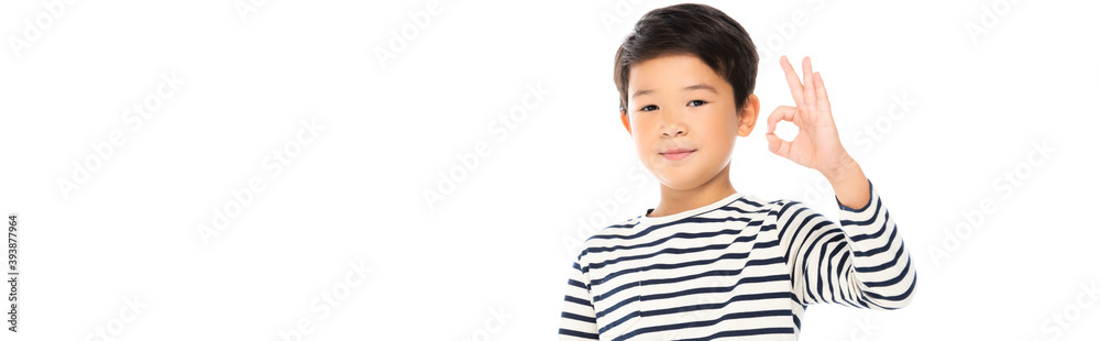 Fototapeta Asian schoolboy showing okay gesture and looking at camera isolated on white, banner