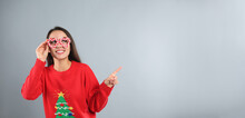 Young Woman In Christmas Sweater And Party Glasses On Grey Background, Space For Text