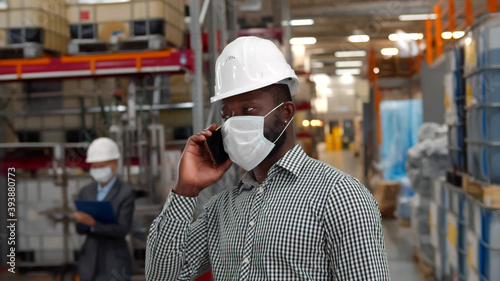 Photo African businessman wearing protective face mask and taking on phone walking in factory warehouse