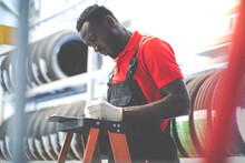 Black Male Mechanic Choose Car Tire At A Tire Store. Expertise Mechanic Working In Automobile Repair Garage.