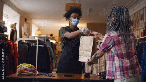 Young woman in safety mask purchasing in clothes store