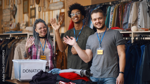 Photo Portrait of young diverse volunteer group with clothes for donation