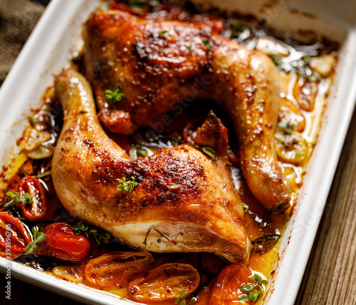 Canvas-taulu Baked chicken leg quarters with herbs and spices served in a baking dish close u