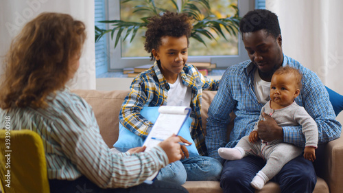 Slika na platnu Social worker consulting smiling young single father with kids at home